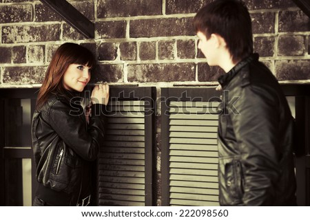 Happy young fashion boy and girl flirting at the wall  - stock photo