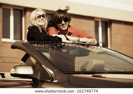 Happy young fashion couple in a convertible car - stock photo