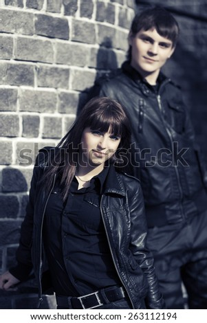 Happy young fashion couple in leather jackets at the brick wall - stock photo