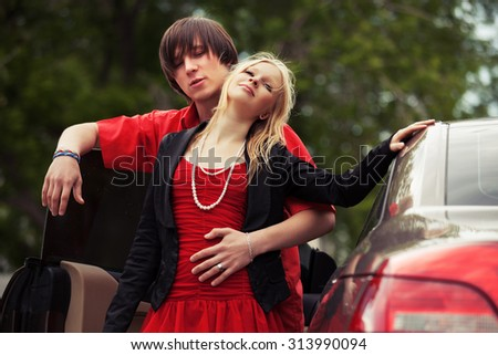 Happy young fashion couple in love by new car - stock photo