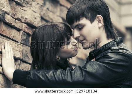 Happy young fashion couple in love on city street - stock photo