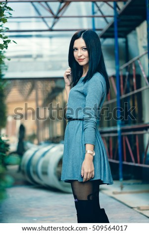 Happy young fashion girl posing with style wearing a grey dress and stockins with her hair in the wind