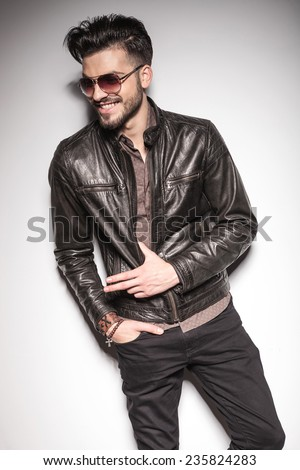 Happy young fashion man smiling while looking away, holding his thumb in his jacket.