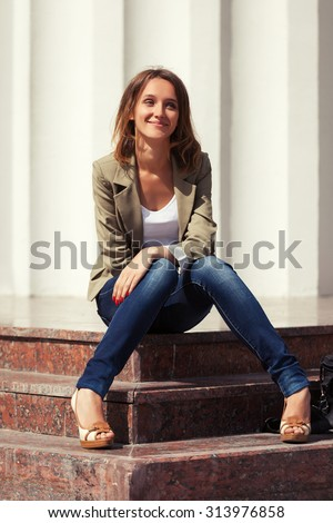 Happy young fashion woman sitting on the mall steps