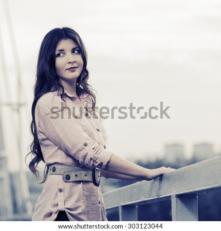 Happy young fashion woman standing on the bridge - stock photo