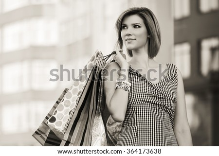 Happy young fashion woman with shopping bags at the mall - stock photo
