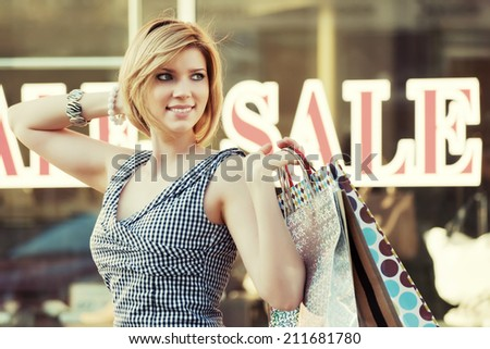 Happy young fashion woman with shopping bags at the mall windows  - stock photo