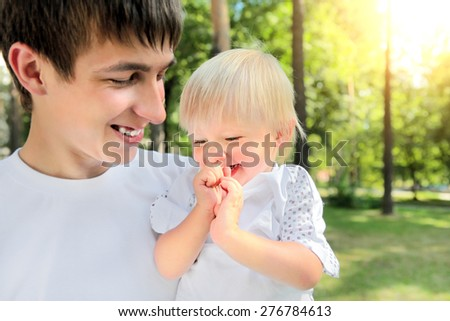 Happy Young Father and Cheerful Child in the Summer Park
