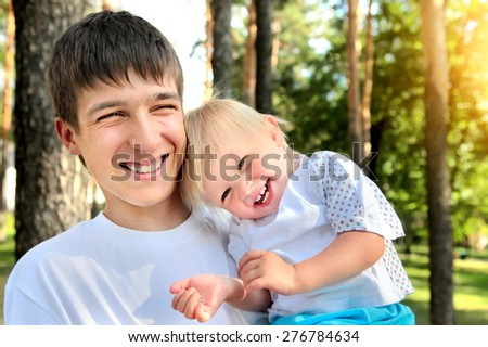 Happy Young Father and Cheerful Child in the Summer Park - stock photo