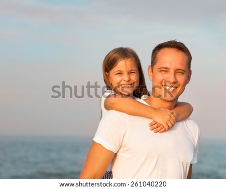 Happy young father and his daughter playing on the beach at the sunny day  - stock photo