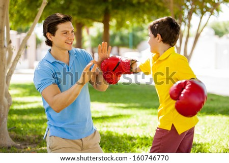 Happy young father and his son having some fun together and boxing at a park - stock photo