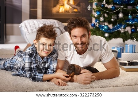 Happy young father and son lying on floor at christmas time, playing with adorable dachshund puppy received for christmas.