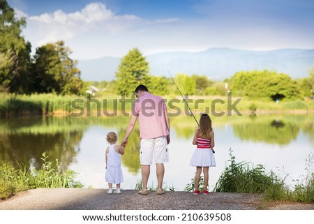 Happy young father fishing on the lake with his little daughters - stock photo