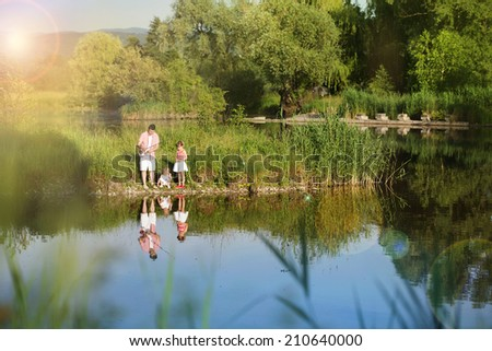 Happy young father fishing on the lake with his little daughters, reflecting in the water - stock photo