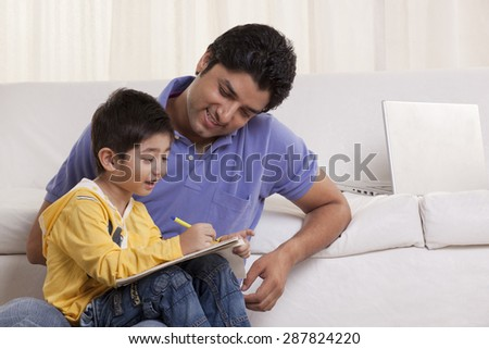 Happy young father helping his son in drawing at home - stock photo