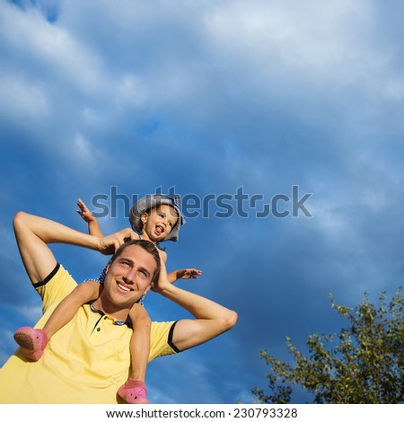 Happy young father holding his little daughter on shoulders against blue sky - stock photo