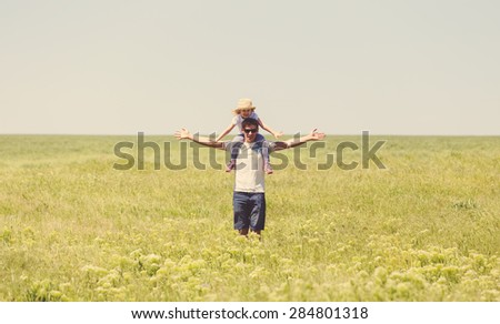 Happy young father holding his little daughter on shoulders against summer meadow - stock photo