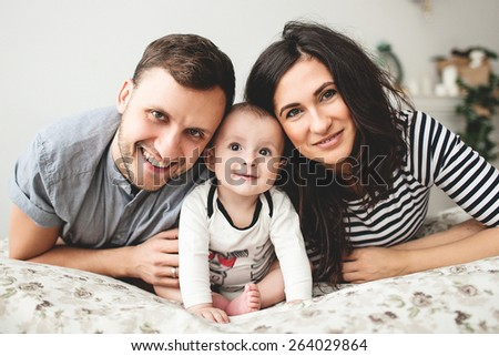 Happy young father, mother and cute baby boy lying on bed - stock photo