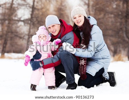 happy young father, mother and their daughter spending time outdoor in the winter park - stock photo