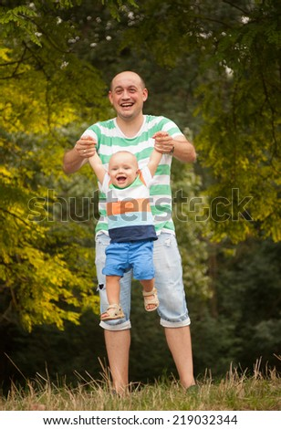 happy young father playing with his little son on the nature on a summer day - stock photo