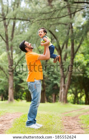 happy young father playing with son outdoors - stock photo