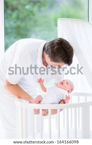 Happy young father putting his newborn baby in a white crib standing next to a big window - stock photo