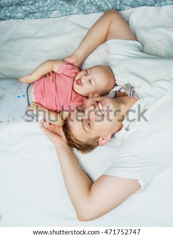 happy young father with a baby  in bed at home