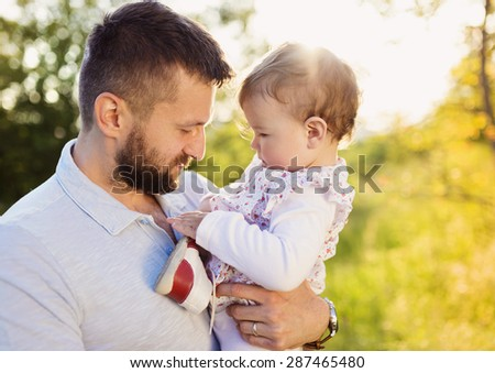 Happy young father with his daughter having fun outside in spring nature - stock photo