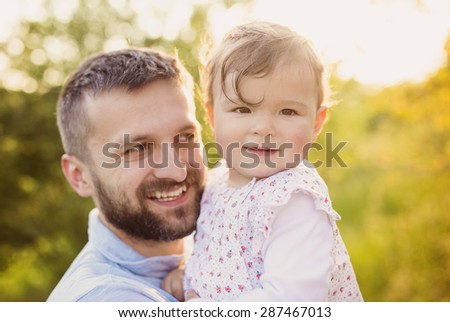 Happy young father with his daughter having fun outside in spring nature
