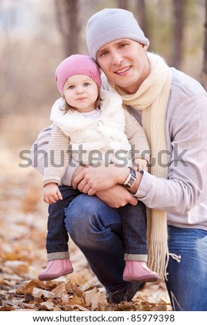 happy young father with his daughter spending time outdoor in the autumn park - stock photo