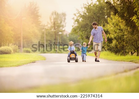 Happy young father with his two little sons have fun on road, one boy is riding on little tractor, other boy is holding father�s hand - stock photo