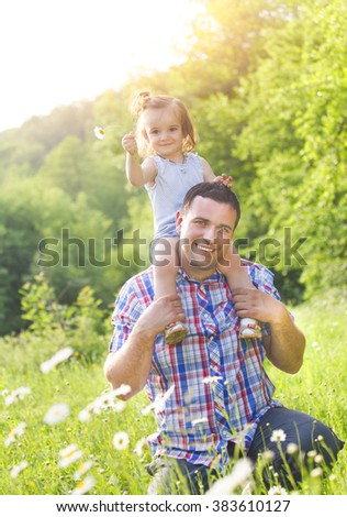 Happy young father with little baby daughter outdoors