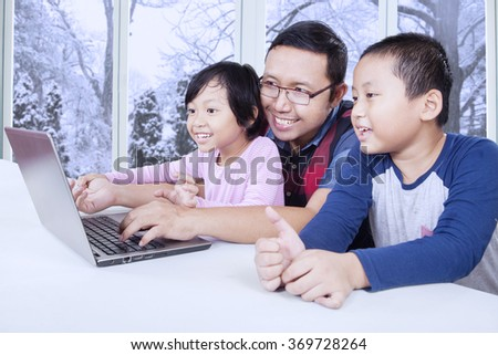 Happy young father with two children using laptop computer at home near the window with winter background - stock photo