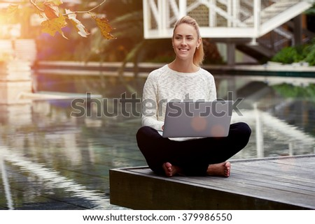 Happy young female admires something beautiful while sitting with open net-book on knees in park, charming woman with smile thinking about wonderful journey while working on laptop computer outside - stock photo