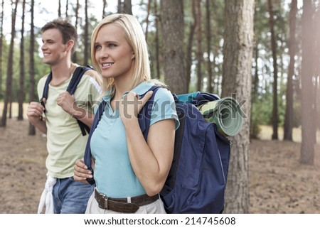 Happy young female backpacker with man hiking in woods - stock photo