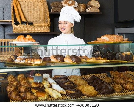 Happy young female baker offering pastry in the confectionery shop