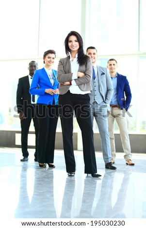 happy young female business leader standing in front of her team  - stock photo