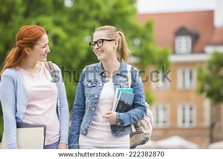 Happy young female college friends walking outdoors - stock photo