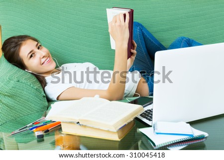 Happy young female college student study in livingroom at home - stock photo