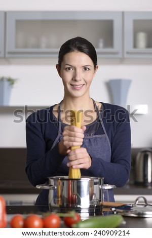 Happy young female cook preparing Italian spaghetti standing at the hob holding a handful of uncooked pasta over a stainless steel saucepan, fresh ingredients in the foreground - stock photo