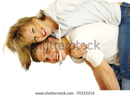 Happy young female enjoying a piggyback ride on boyfriends back against white - stock photo