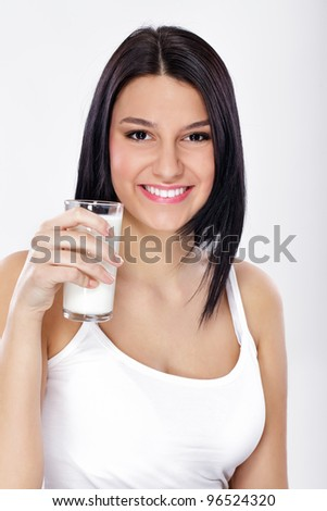 Happy young female holding a glass of fresh milk - stock photo