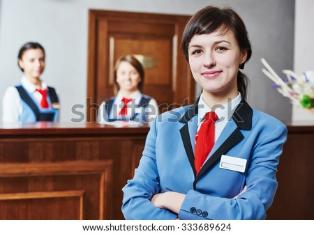 Happy young female hotel receptionist worker standing at reception - stock photo