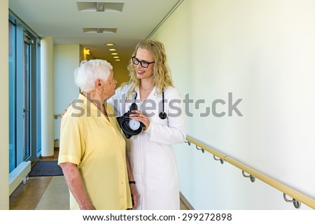 Happy Young Female Nurse with Blood Pressure Apparatus, Assisting an Elderly Woman at the Corridor Inside the Hospital.