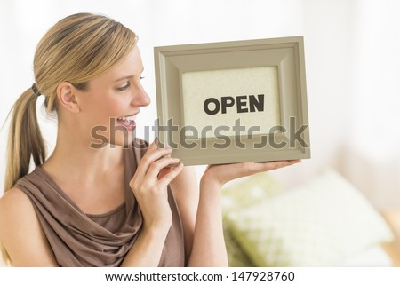 "Happy young female owner holding ""open"" sign in bedding store - stock photo"