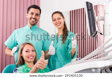 Happy young female patient and smiling dental clinic crew. Focus on girl
