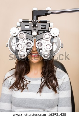 Happy young female patient looking through phoropter during eye exam - stock photo