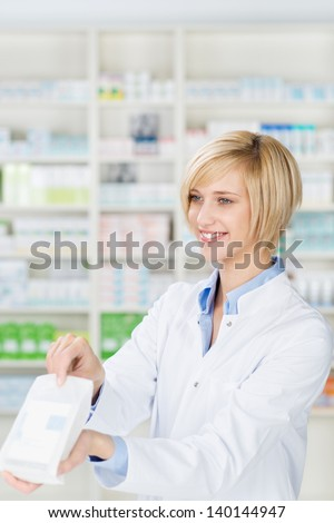 Happy young female pharmacist giving prescription medicines in pharmacy