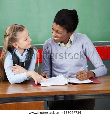 Happy young female professor looking at little schoolgirl at desk in classroom