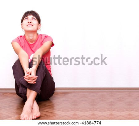 Happy young female sitting relaxed by the wall on the floor - stock photo